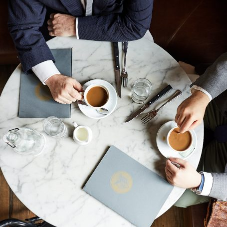 top-down view of table with 2 men drinking coffee